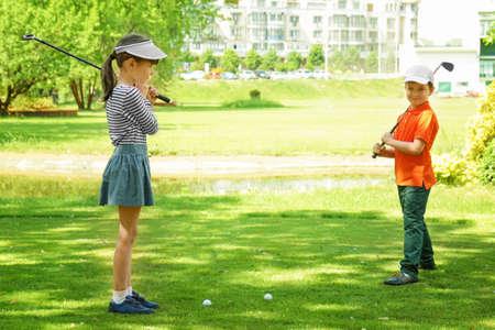 Nette Kinder, die am sonnigen Tag Golf auf Kurs spielen