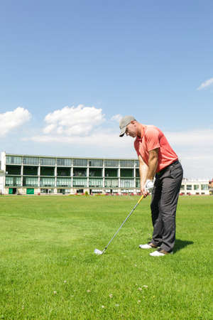 Young man playing golf on course in sunny day
