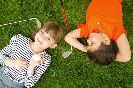 Nette Kinder mit Ball und Fahrern, die auf Golfplatz liegen