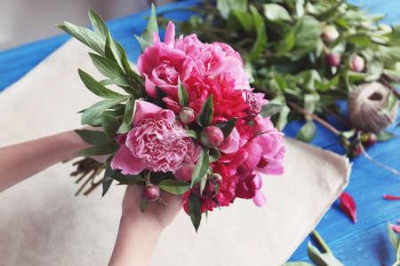 Female florist making bouquet of beautiful peonies in flower shop, closeup