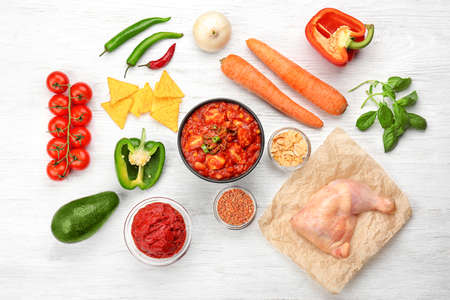 Composition with delicious turkey chili and ingredients on wooden background Stock Photo