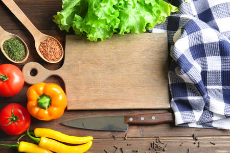 Wooden board with vegetables on kitchen table. Cooking classes concept