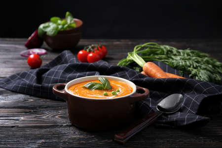 Tureen with delicious carrot soup on table
