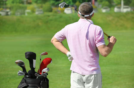 Young man on golf course in sunny day Stock Photo