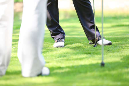 Legs of young men playing golf on course in sunny day