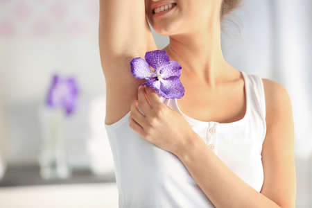 Beautiful young woman with flower at home, closeup. Epilation concept 스톡 콘텐츠