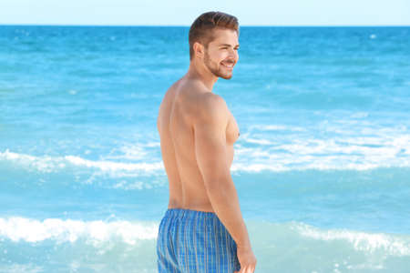Handsome young muscular man in swimwear on sea background Archivio Fotografico - 101696718