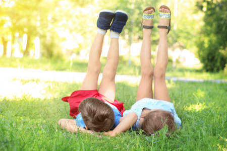 Cute little children lying on green grass in park