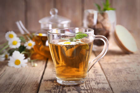 Cup of chamomile tea on wooden background