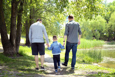 Gay couple with son in park 스톡 콘텐츠