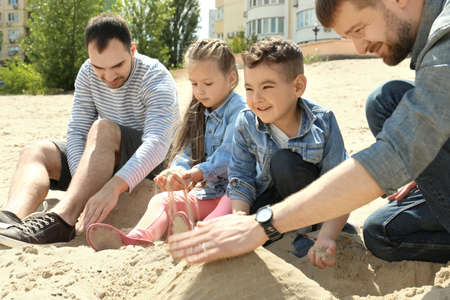 Male gay couple with children playing on sand