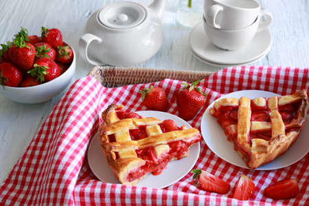 Plates with delicious strawberry cake in tray on table