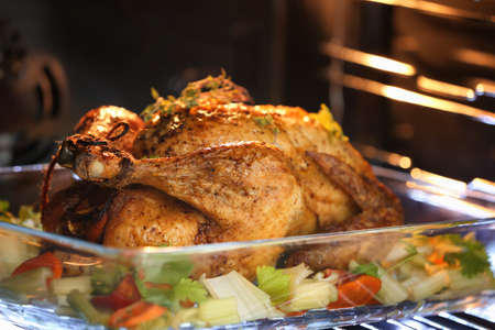 Golden roasted turkey and vegetables on baking dish in oven