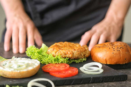 Woman cooking tasty turkey burger at table