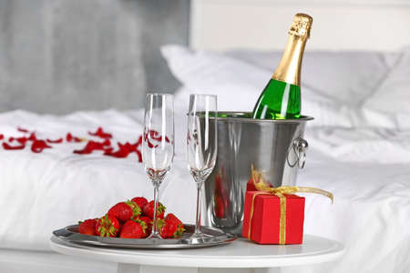 Romantic composition with champagne and strawberry on table in bedroom. Honeymoon concept Stock Photo