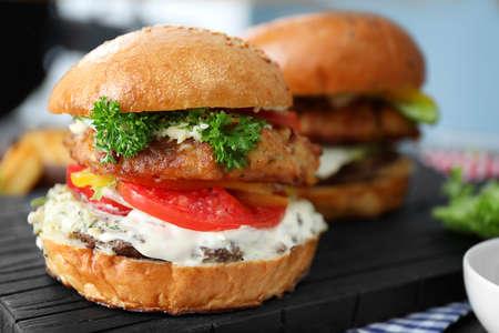 Tasty turkey burger on wooden board