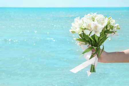 Woman holding beautiful bouquet on blue sea background. Beach wedding concept