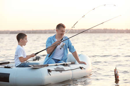 Dad and son fishing from inflatable boat on river Banque d'images