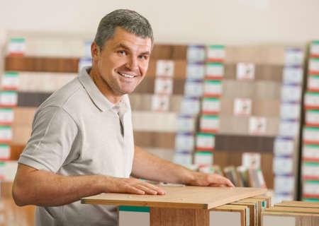 Mature man choosing laminate samples in hardware store