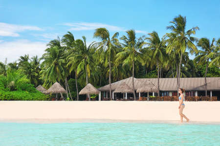 Beautiful young woman on sea beach at resort
