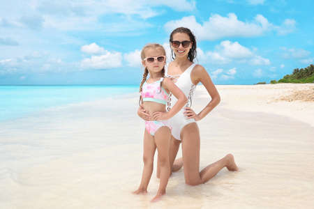 Beautiful young woman with her daughter on beach at sea resort