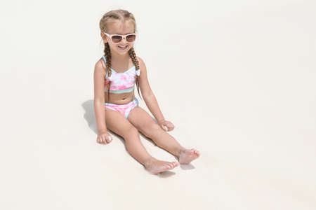 Cute little girl sitting on beach sand at sea resort