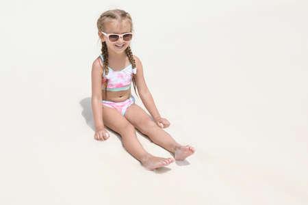 Cute little girl sitting on beach sand at sea resort