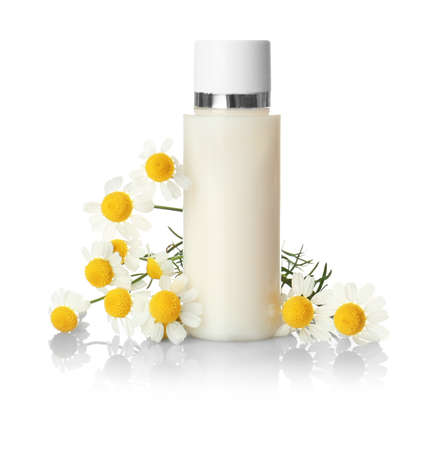 Bottle of essential oil and chamomile flowers on white background