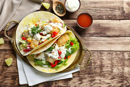 Metal tray with tasty fish tacos and sauce on table Stock Photo