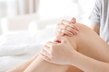 Young woman suffering from pain in leg at home Stock Photo