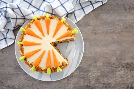 Delicious sliced carrot cake on table