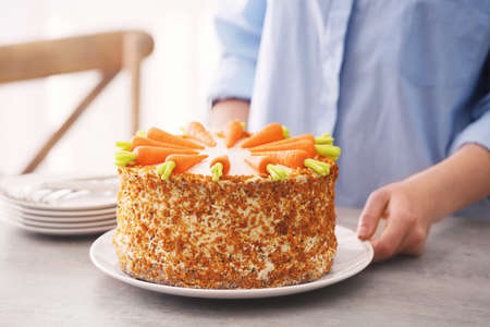 Young woman with delicious carrot cake on table Stock Photo