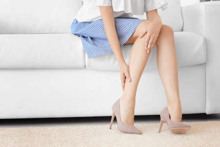Young woman suffering from leg pain at home Standard-Bild