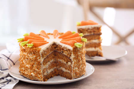 Delicious sliced carrot cake on blurred background