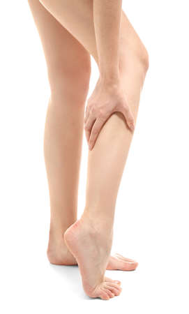 Young woman suffering from leg pain on white background Stock Photo