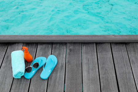 Beach accessories on wooden pontoon at sea resort. Summer vacation concept Imagens