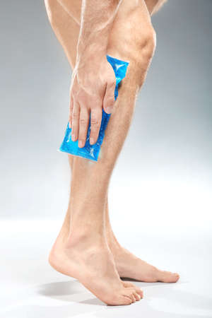 Young man applying cold compress to leg on light background