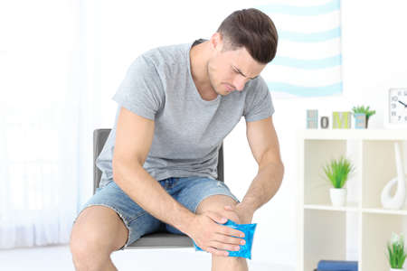 Young man applying cold compress to leg at home