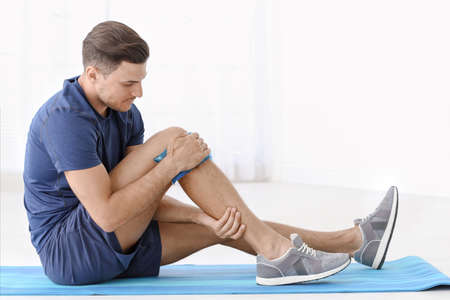 Young man suffering from pain in leg at home Stock Photo