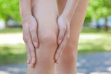 Young woman suffering from pain in leg, outdoors Stock Photo