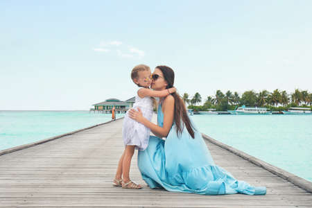 Beautiful young woman with her daughter at sea resort 版權商用圖片