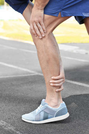 Young man suffering from pain in leg, outdoors