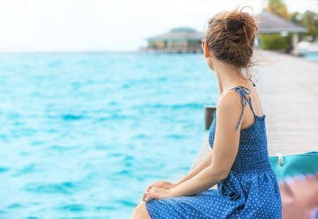 Beautiful young woman sitting on pontoon at sea resort Imagens