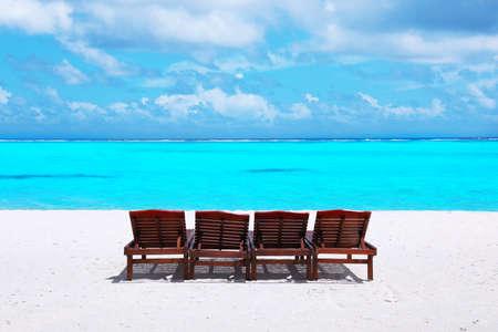Wooden sun loungers on sea beach in summer day Stock Photo