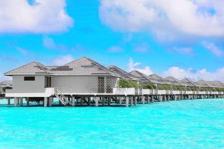 Modern beach houses on piles at tropical resort Imagens