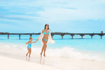 Beautiful young woman with daughter on sea beach