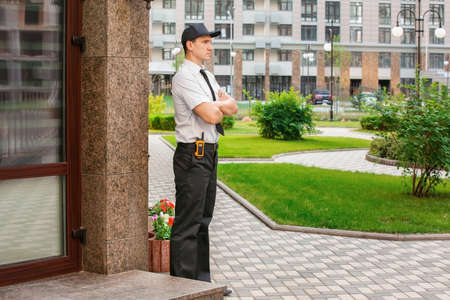 Male security guard near building, outdoors Stock Photo
