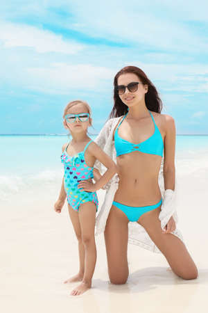 Cute little girl with mother on sea beach