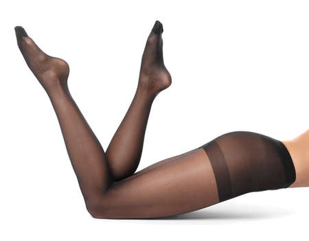 Legs of beautiful young woman in black tights on white background