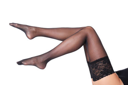 Legs of beautiful young woman in black stockings on white background